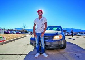 Scribe Opinion Editor and Uber driver Alexander Nedd stands in front of his Chevy Cobalt. Megan Lunsford | The Scribe