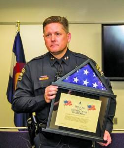 Police Chief Brian McPike holds the flag during the presentation. Austin Chasse | The Scribe