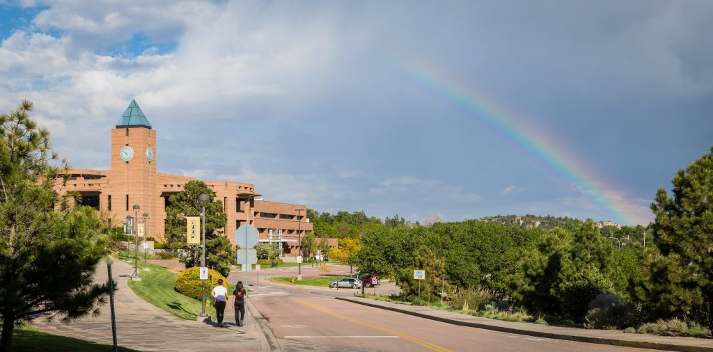 Students walking towards bell tower with rainbow in the background.