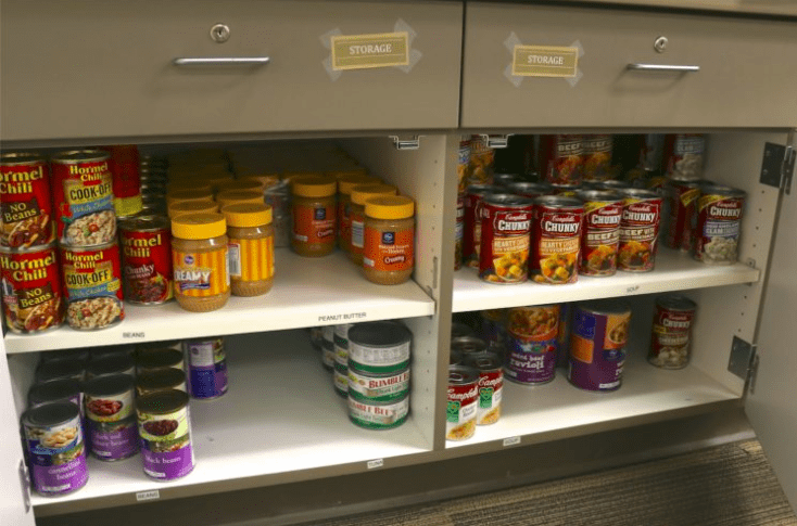 Canned food sitting on shelves inside of a pantry.