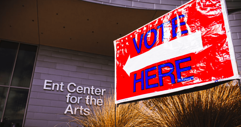 A 'vote here' sign pointing towards the Ent center for the arts.